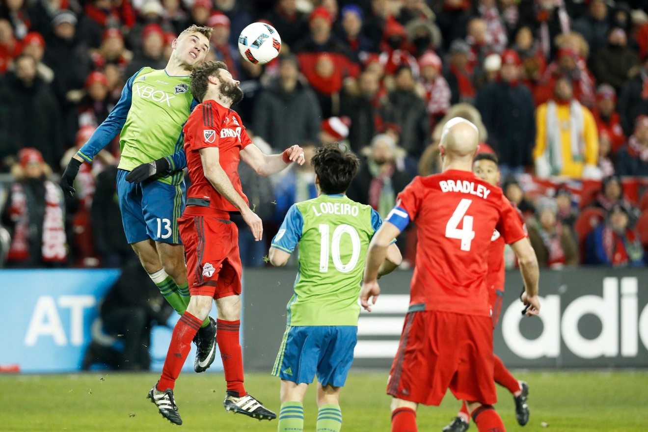Toronto FC defender Drew Moor (3) jumps to head the ball against Seattle Sounders forward Jordan Morris (13) as Sounders midfielder Nicolas Lodeiro (10) and Toronto FC midfielder Michael Bradley (4) look on during first-half MLS Cup final soccer action in Toronto, Saturday, Dec. 10, 2016. (Mark Blinch/The Canadian Press via AP)