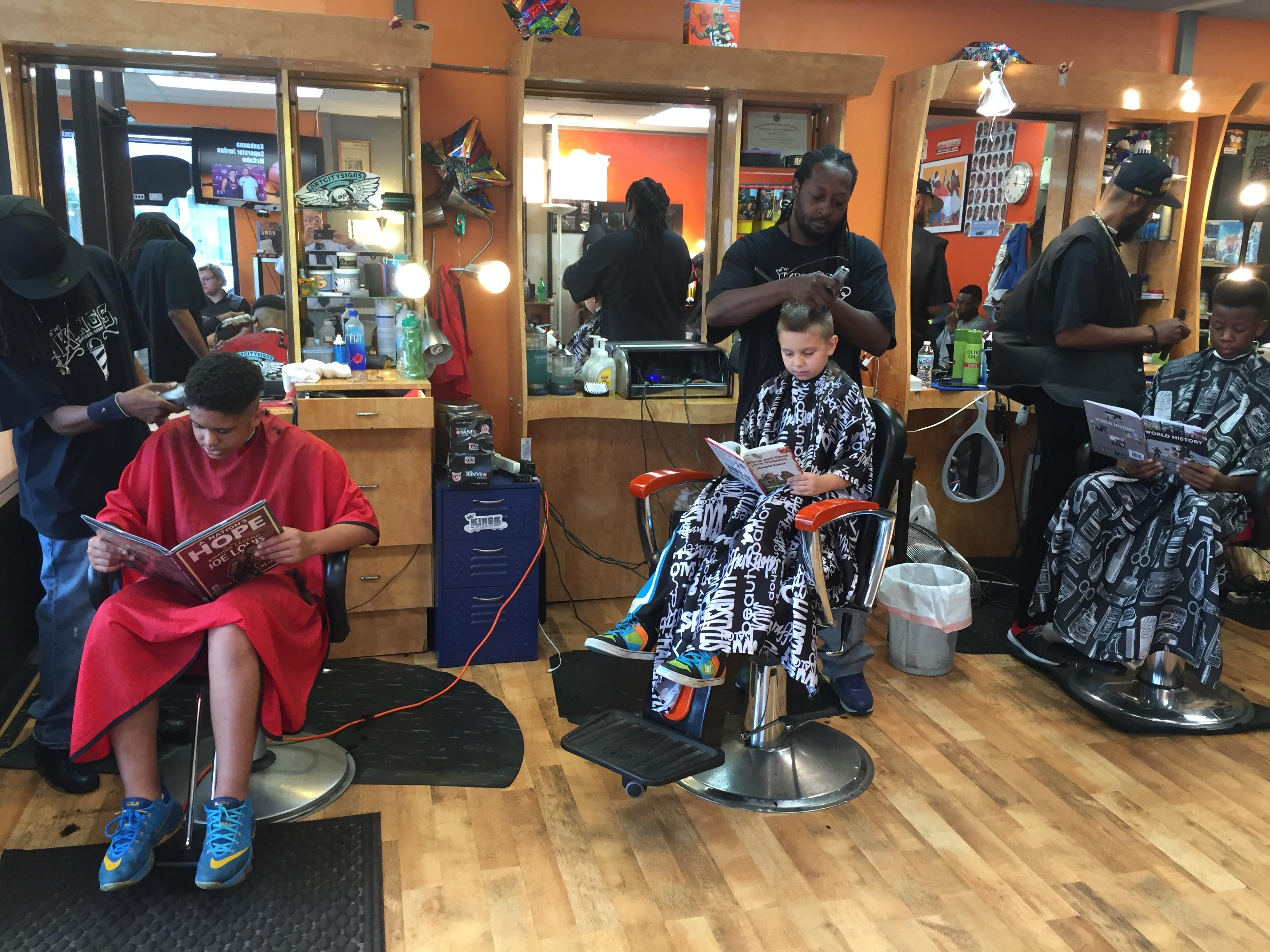Children read books while they have their hair cut during Read to Cut Aug. 28, 2017, at Kings Barber Shop in Appleton. (WLUK/Eric Peterson)