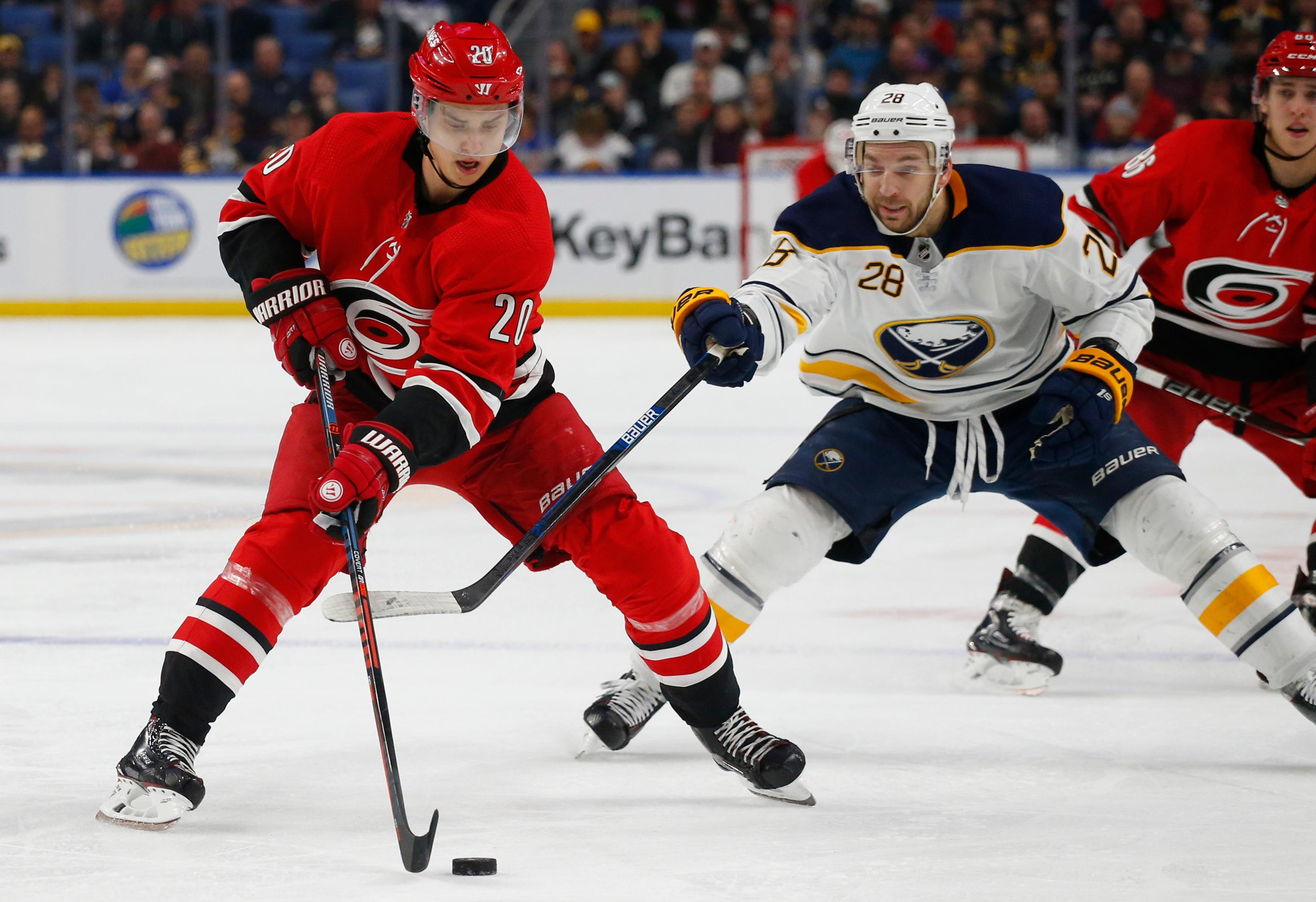 Buffalo Sabres forward Zemgus Girgensons (28) stick checks Carolina Hurricanes forward Sebastian Aho (20) during the second period of an NHL hockey game Thursday, Feb. 7, 2019, in Buffalo N.Y. (AP Photo/Jeffrey T. Barnes)