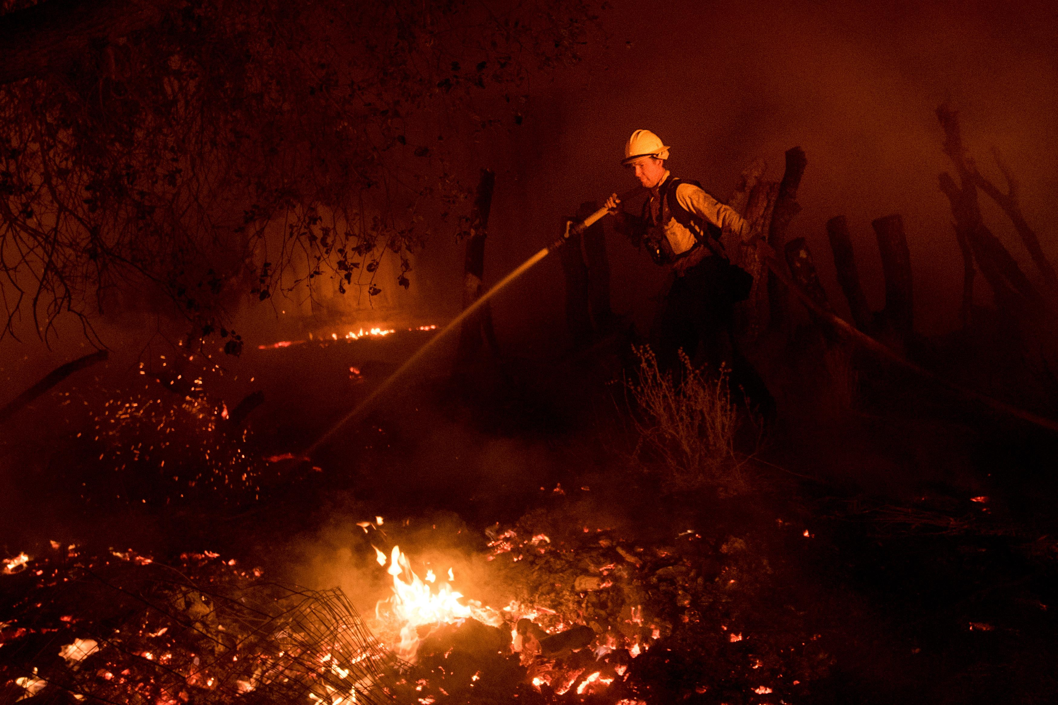 A firefighter battles a wildfire in Ojai, Calif., on Thursday, Dec. 7, 2017. (AP Photo/Noah Berger)