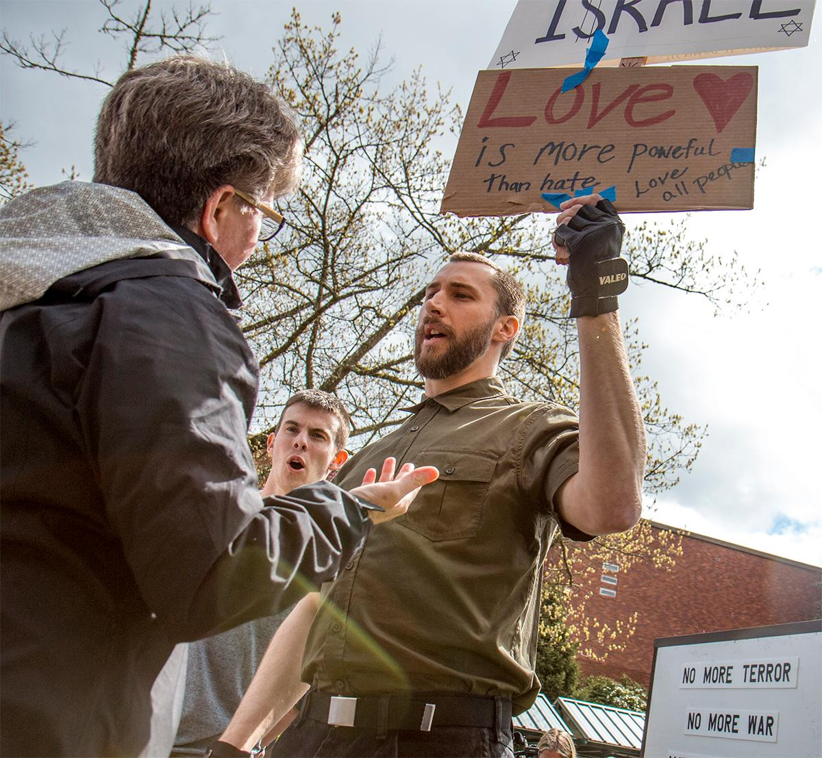"Upon saying that he agreed with another sign a member of the crowd places that sign below his in an attempt to calm the crowds rising anger. Neo-Nazis momentarily caused a stir outside the EMU on the University of Oregon campus. According to a man in the crowd they were promoting a holocaust denial film. While some UO students engaged in debate with the two men, others shouted at them to ""go home,"" and that they ""didn't want them here."" The two men soon drove away in their car to the applause of the crowd. Photo by August Frank, Oregon News Lab"