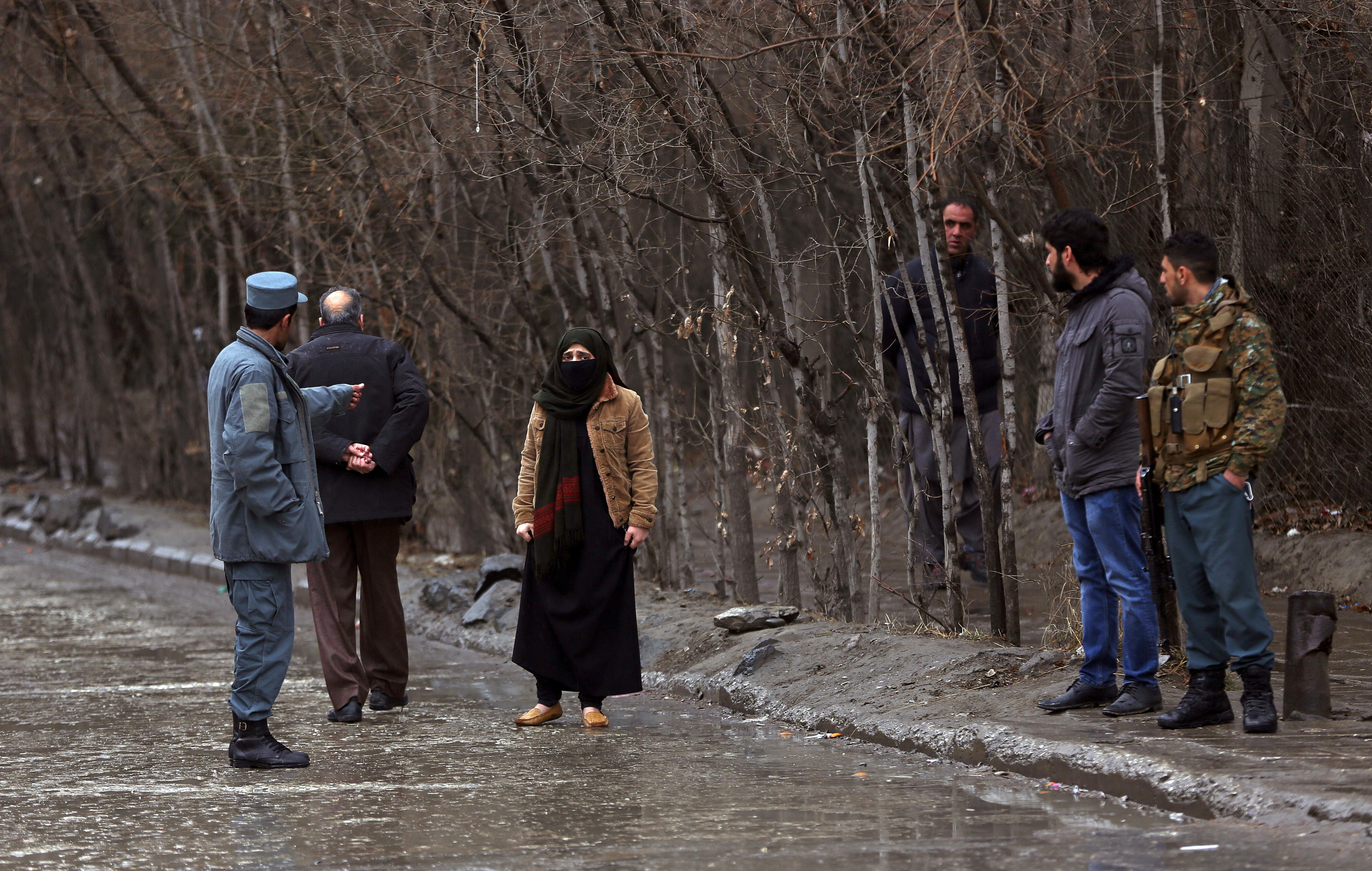 A woman talks with a police officer as her relative was at site of a suicide bombing in the diplomatic area of capital Kabul, Afghanistan, Saturday, Feb. 24, 2018. Interior ministry spokesman Najib Danish said several people were wounded in Saturday's attack in the Shash Darak area of Kabul, near NATO headquarters and not far from the U.S. Embassy. (AP Photo/Massoud Hossaini)