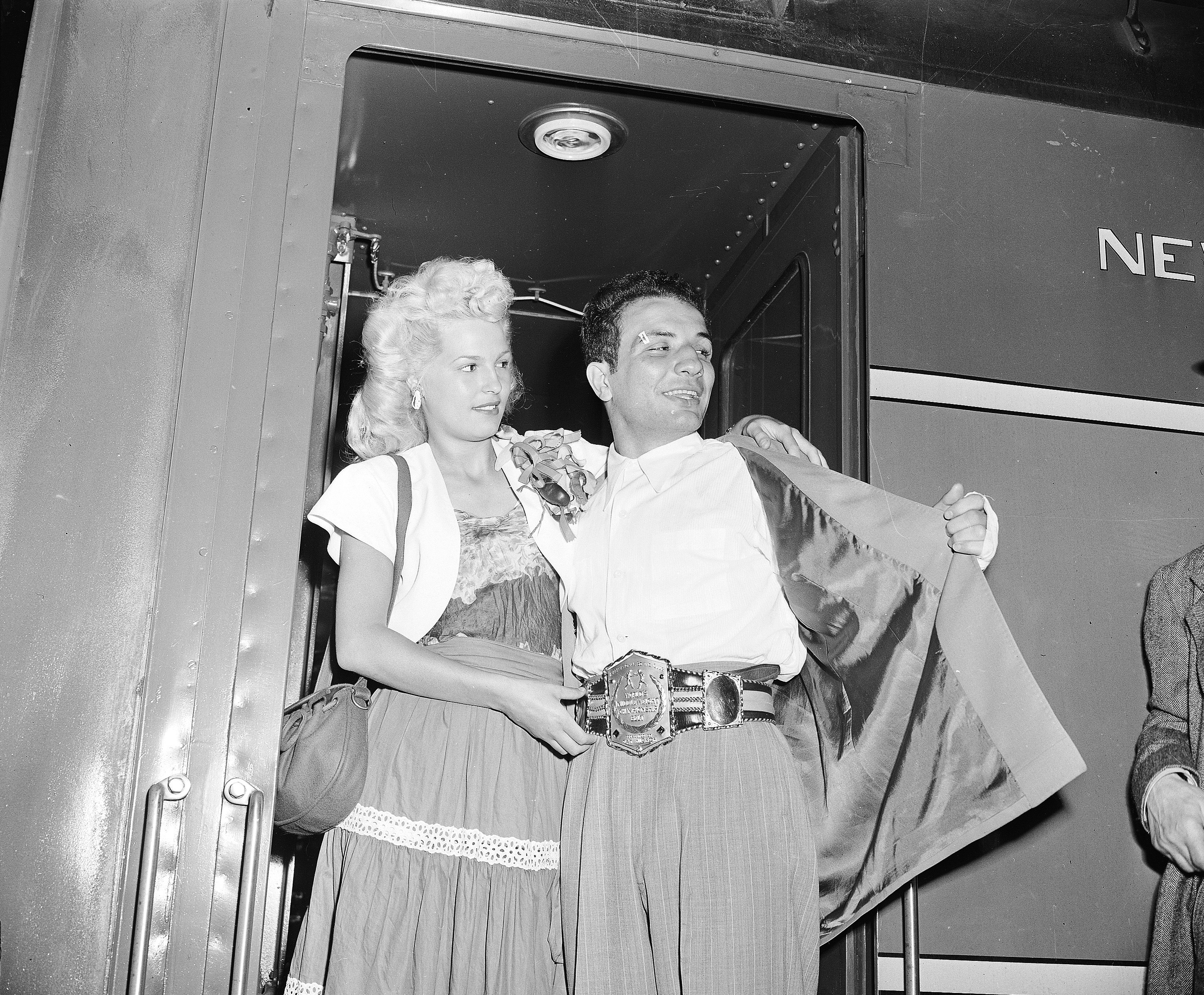 "FILE - In this June 18, 1949, file photo, newly crowned World Middleweight Boxing Champion Jake LaMotta, accompanied by his wife Vicky, arrives at Grand Central Terminal in New York after defeating Marcel Cerdan in Detroit on June 16. LaMotta, whose life was depicted in the film ""Raging Bull,"" died Tuesday, Sept. 19, 2017, at a Miami-area hospital from complications of pneumonia. He was 95. (AP Photo/File)"