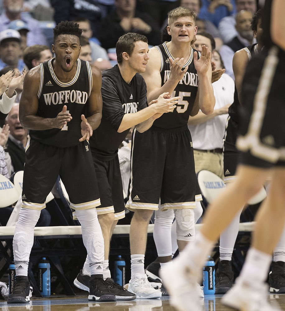 Wofford's Derrick Brooks (1) leads the cheers from the bench as the team celebrates a lead over North Carolina during the final minute of an NCAA college basketball game Wednesday, Dec. 20, 2017, in Chapel Hill, N.C. (Robert Willett/The Herald-Sun via AP)