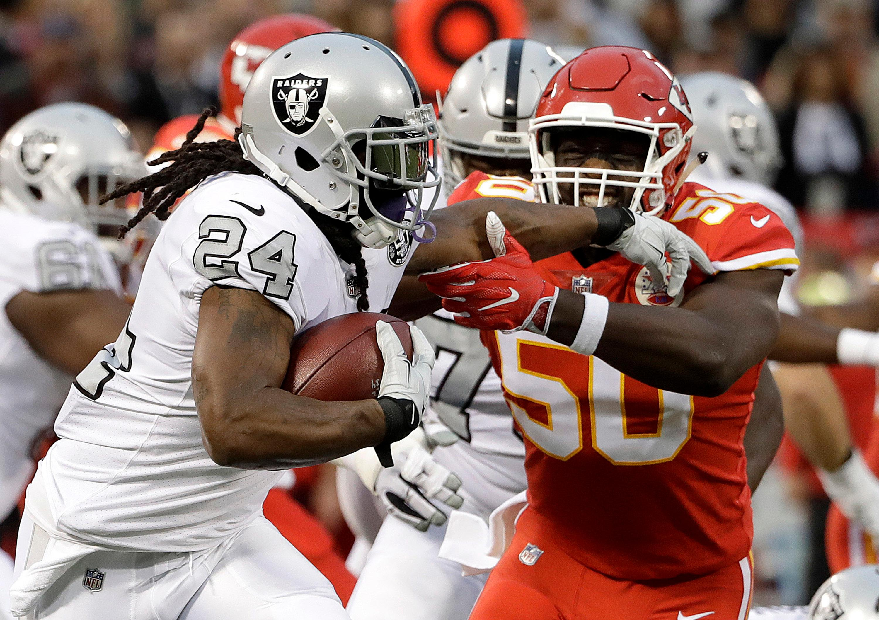 Oakland Raiders running back Marshawn Lynch (24) runs against Kansas City Chiefs outside linebacker Justin Houston (50) during the first half of an NFL football game in Oakland, Calif., Thursday, Oct. 19, 2017. (AP Photo/Marcio Jose Sanchez)