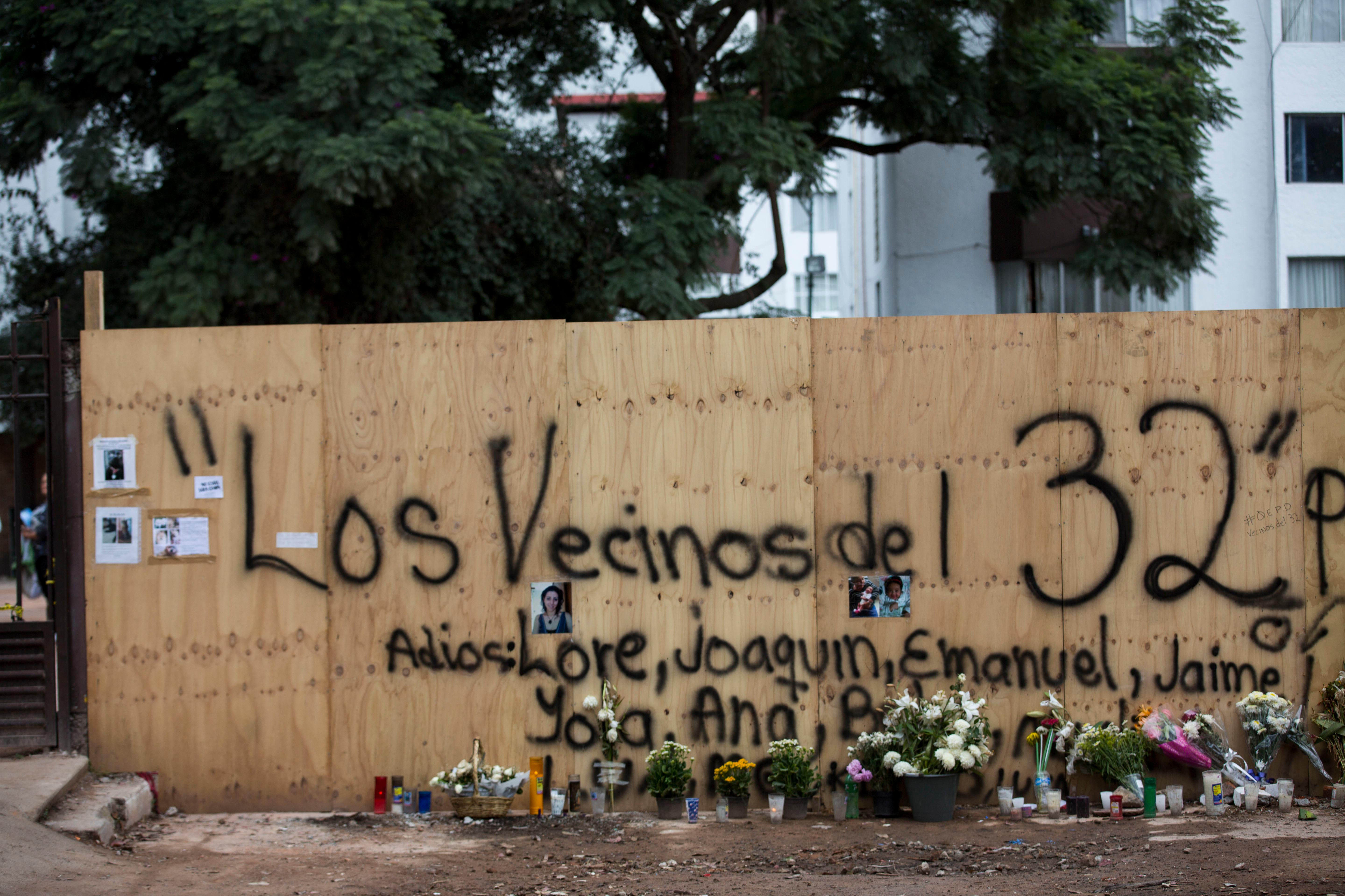 "A plywood barrier fence shielding the spot where a six-story apartment building collapsed, killing a dozen people, someone spray-painted on the fence, ""to the neighbors of 32,"" the number of the apartment block that collapsed, in Mexico City, Thursday, Sept. 28, 2017.  (AP Photo/Moises Castillo)"