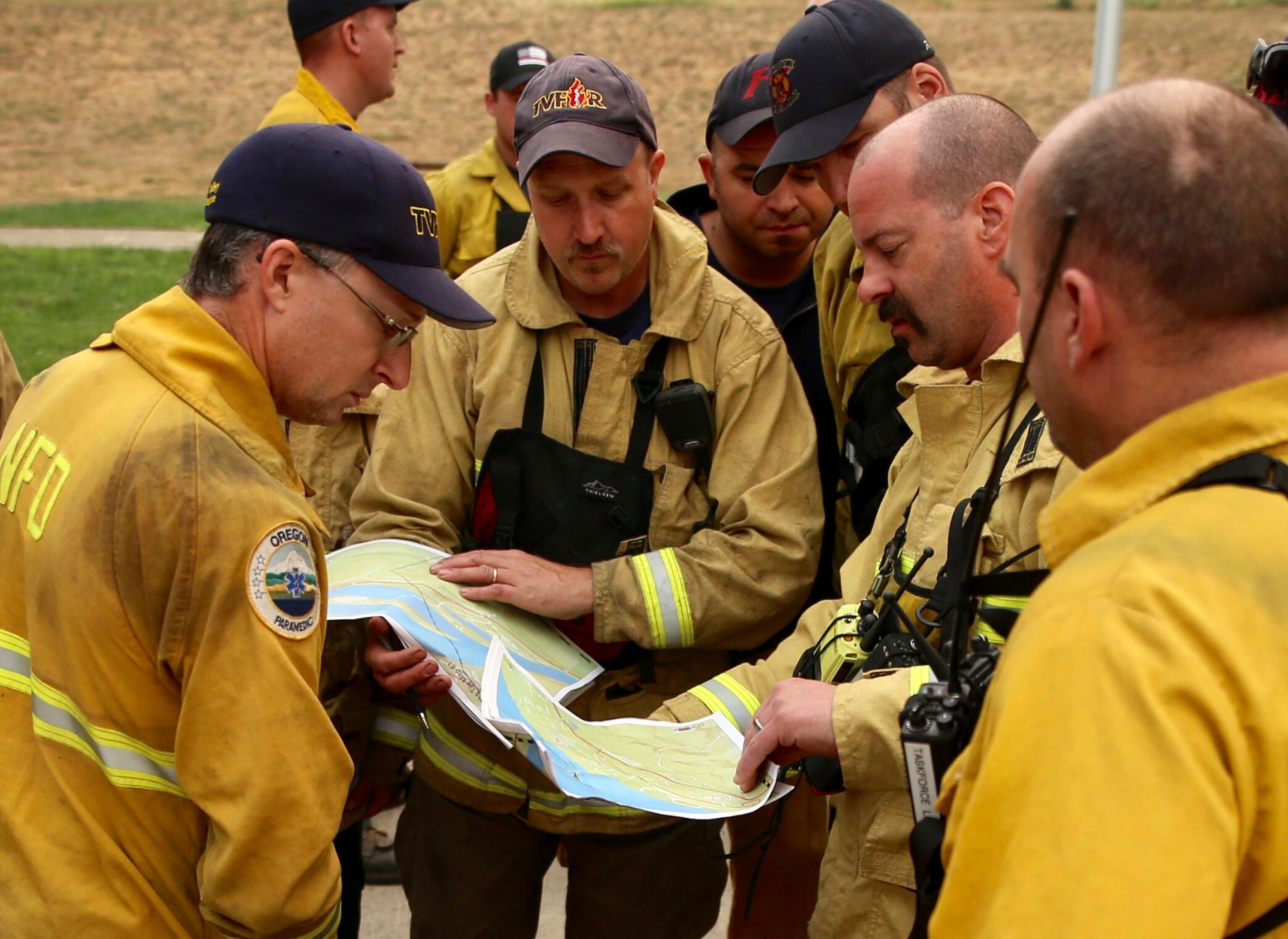 Firefighters look over maps in Cascade Locks, Ore., Wednesday, Sept. 6, 2017, near where the Eagle Creek wildfire continues to burn. Firefighting crews are in the town in anticipation of west winds possibly pushing the fire into town. (AP Photo/Randy L. Rasmussen)