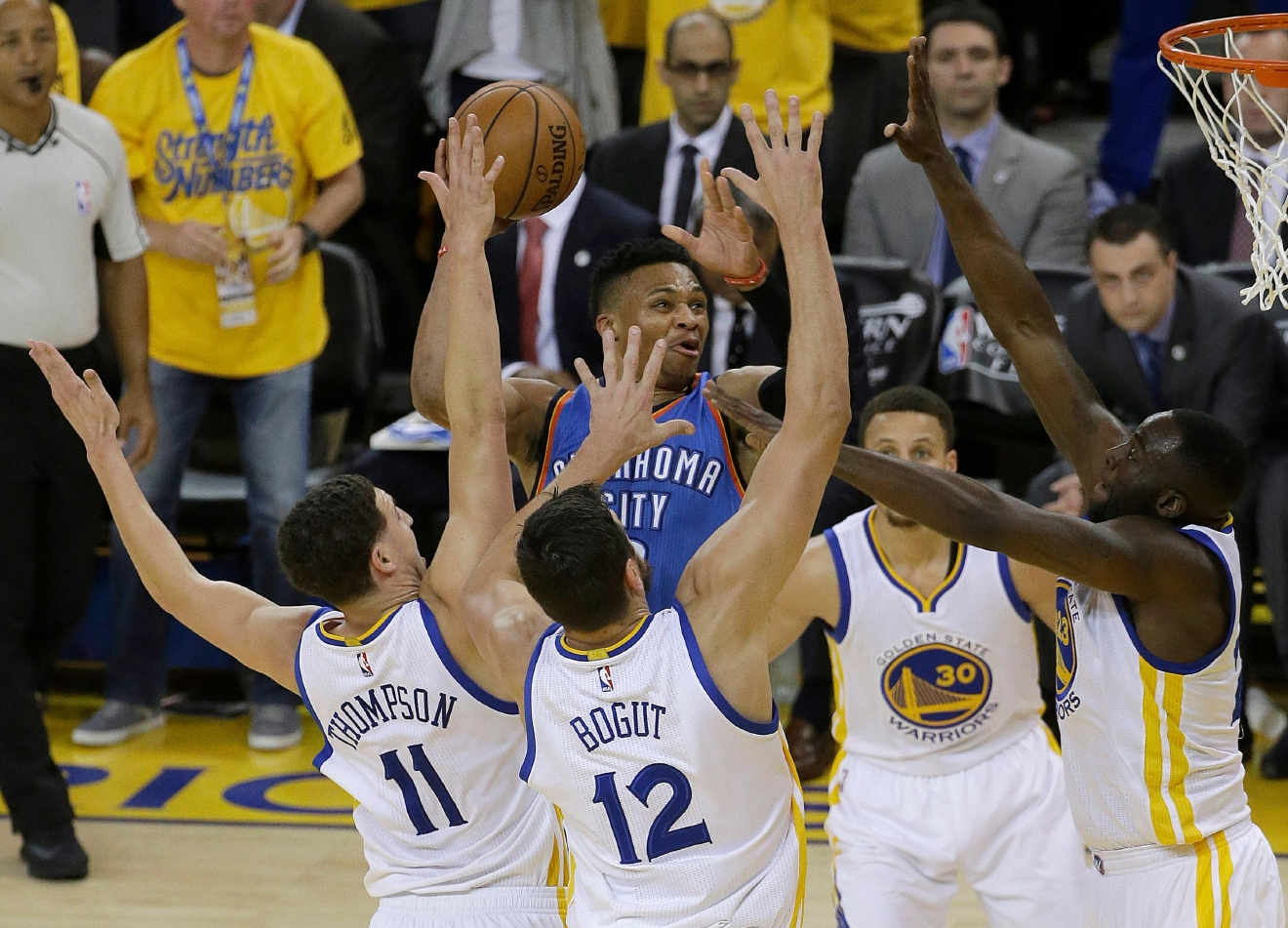 Oklahoma City Thunder guard Russell Westbrook, center, shoots between Golden State Warriors guard Klay Thompson (11), center Andrew Bogut (12) and guard Stephen Curry (30) and forward Draymond Green during the first half of Game 5 of the NBA basketball Western Conference finals in Oakland, Calif., Thursday, May 26, 2016. (AP Photo/Jeff Chiu)
