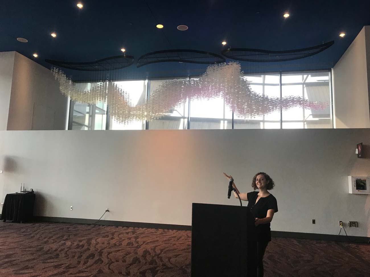 "Pictured: Jessica Wolf / Her piece, ""Confluence"", was designed to be displayed in the Duke Energy Convention Center through a partnership they have with ArtWorks where they curate local art installations to showcase. Confluence is located in the window alcove by the Grand Ballroom, which sits behind the ""A"" in the large Cincinnati sign seen on the west side of the building from outside. She worked with four ArtWorks apprentices who helped cut, fold, and string around 11,000 paper circles to assemble the sculpture. It took over eight weeks to complete. / Image courtesy of Paper Acorn // Published: 6.18.20"