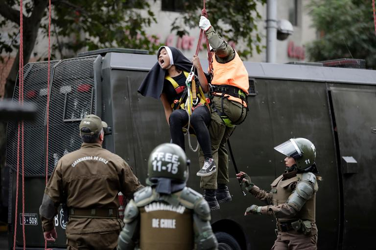 An activist dressed as a nun is lowered down by a police officers, and detained, after she and other protesters placed a pro-abortion banner above a road near Pope Francis' expected route, before the pontiff's arrival in Santiago, Chile, Monday, Jan. 15, 2018. (AP Photo/Victor R. Caivano)