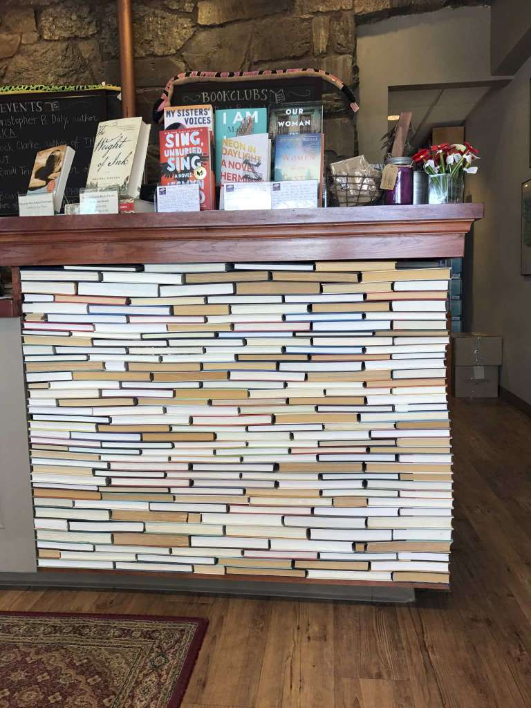 This undated photo shows the check-out counter at the indie bookseller Newtonville Books in Newton, Mass. The counter is made of rows of backwards books glued into place. (Tracee M. Herbaugh via AP)