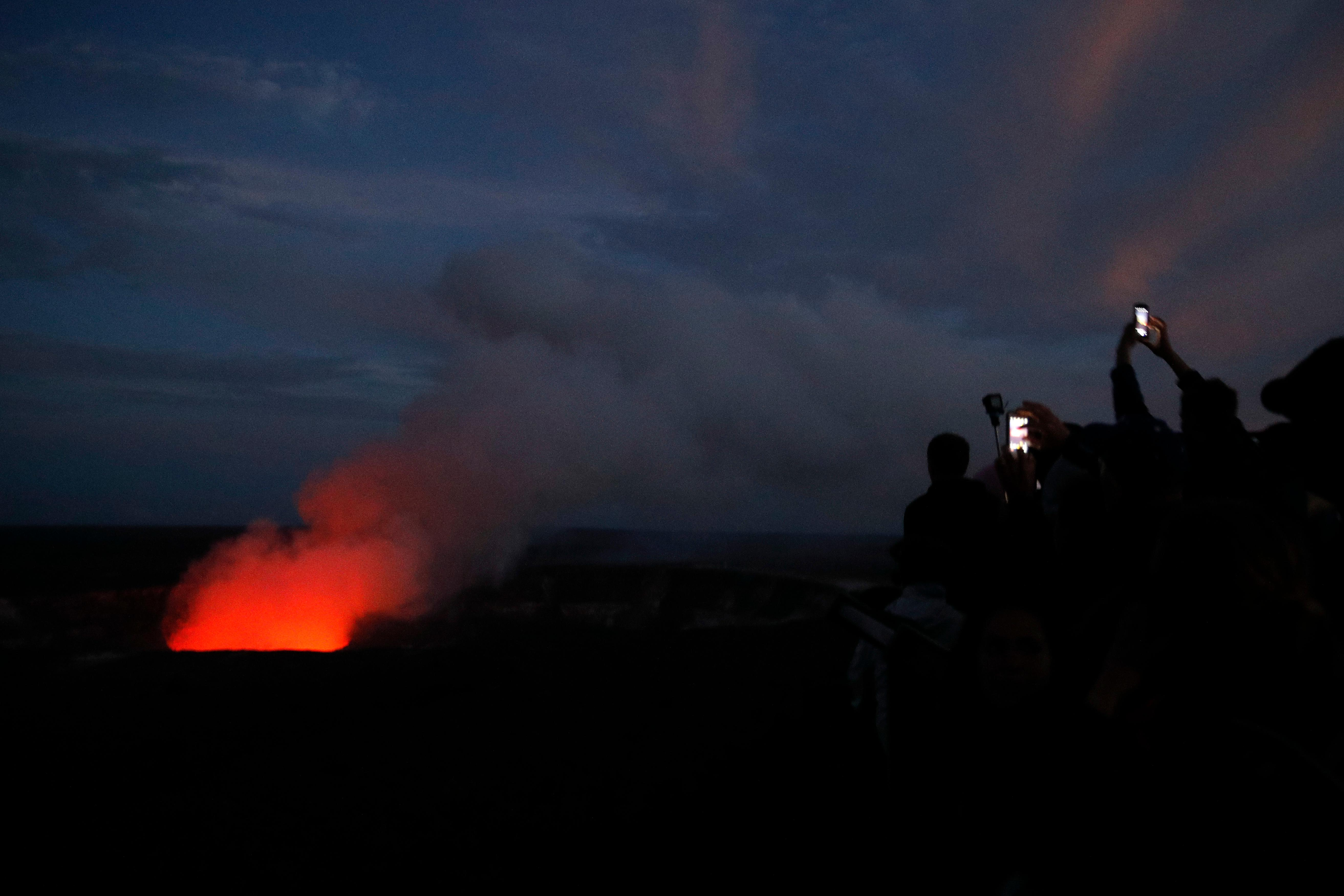 Visitors take pictures as Kilauea's summit crater glows red in Volcanoes National Park, Hawaii, Wednesday, May 9, 2018. Geologists warned Wednesday that Hawaii's Kilauea volcano could erupt explosively and send boulders, rocks and ash into the air around its summit in the coming weeks. (AP Photo/Jae C. Hong)