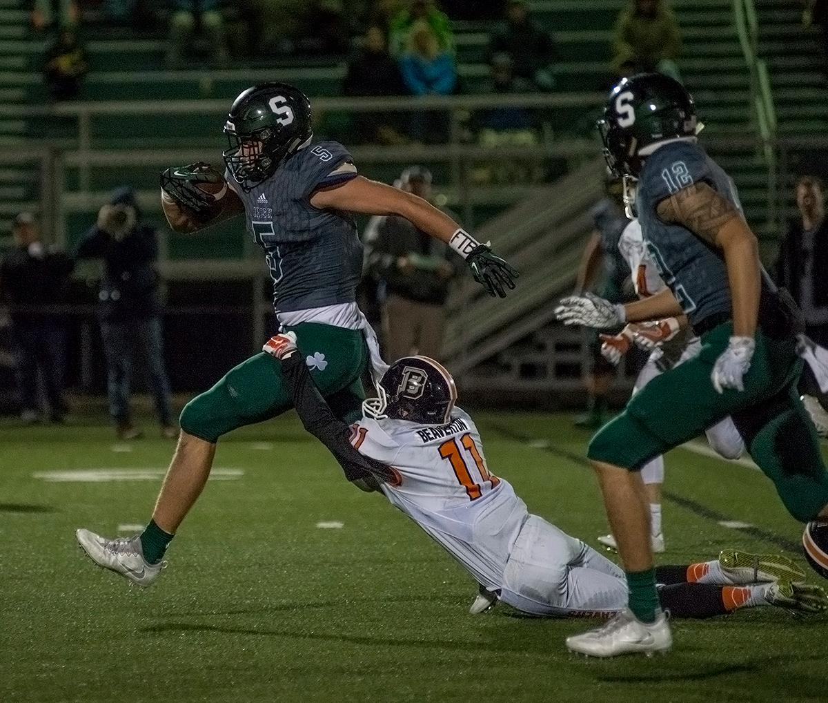 Sheldon Irish wide receiver Patrick Herbert (#5) runs through Beaverton Beavers defensive back Jack Laperle's (#11) tackle. The Sheldon Irish defeated the Beaverton Beavers 48-7 on Friday night at Sheldon in the first round of 6A state playoffs. Photo by Abigail Winn, Oregon News Lab