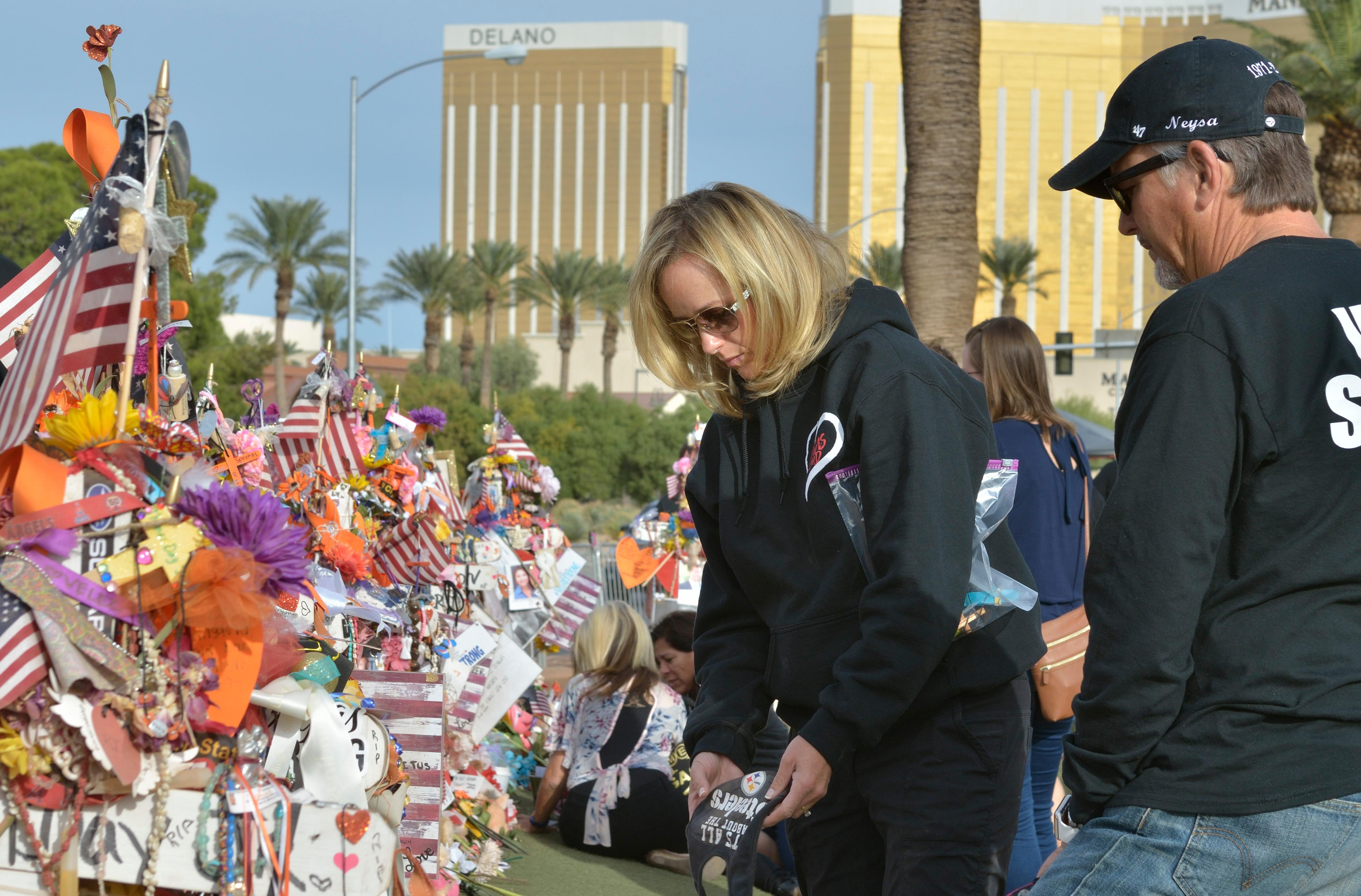 "Mynda Smith and her father Chris Davis are shown near a memorial cross for her sister Neysa Tonks during ""Greg Zanis Day"" at the Welcome to Fabulous Las Vegas sign on the Las Vegas Strip on Sunday, Nov. 12, 2017. Zanis, a carpenter from Aurora, Ill., was recognized by the Clark County Commision for creating 58 crosses memorializing those who died during the Route 91 Harvest festival shooting on Oct. 1. The crosses were later moved to the Clark County Museum for its permanent collection. [Bill Hughes/Las Vegas News Bureau]"