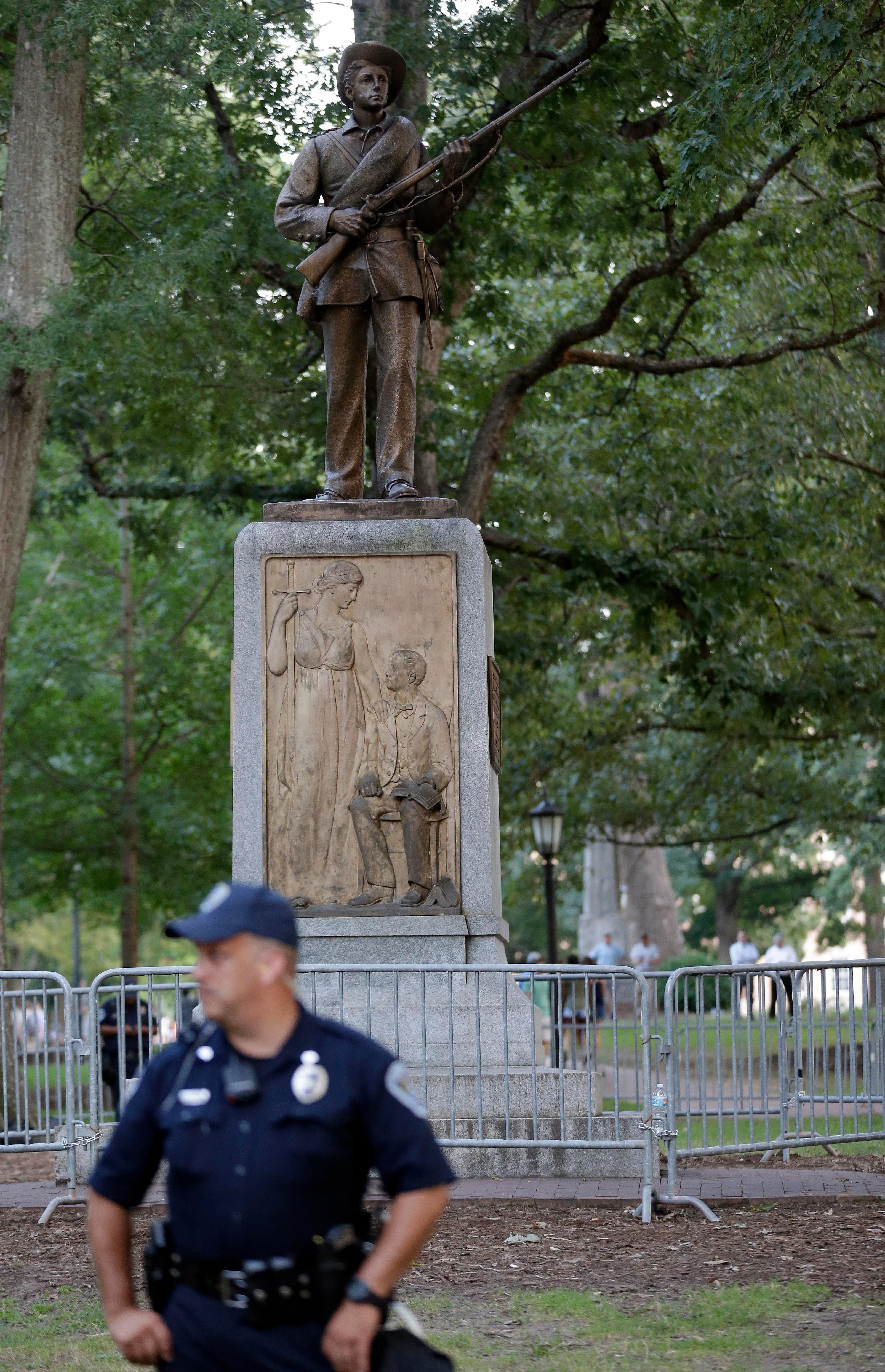 "FILE - In this Aug. 22, 2017, file photo, police stand by a Confederate monument nicknamed ""Silent Sam"" at the University of North Carolina-Chapel Hill in Chapel Hill, N.C. (AP Photo/Gerry Broome, File)"