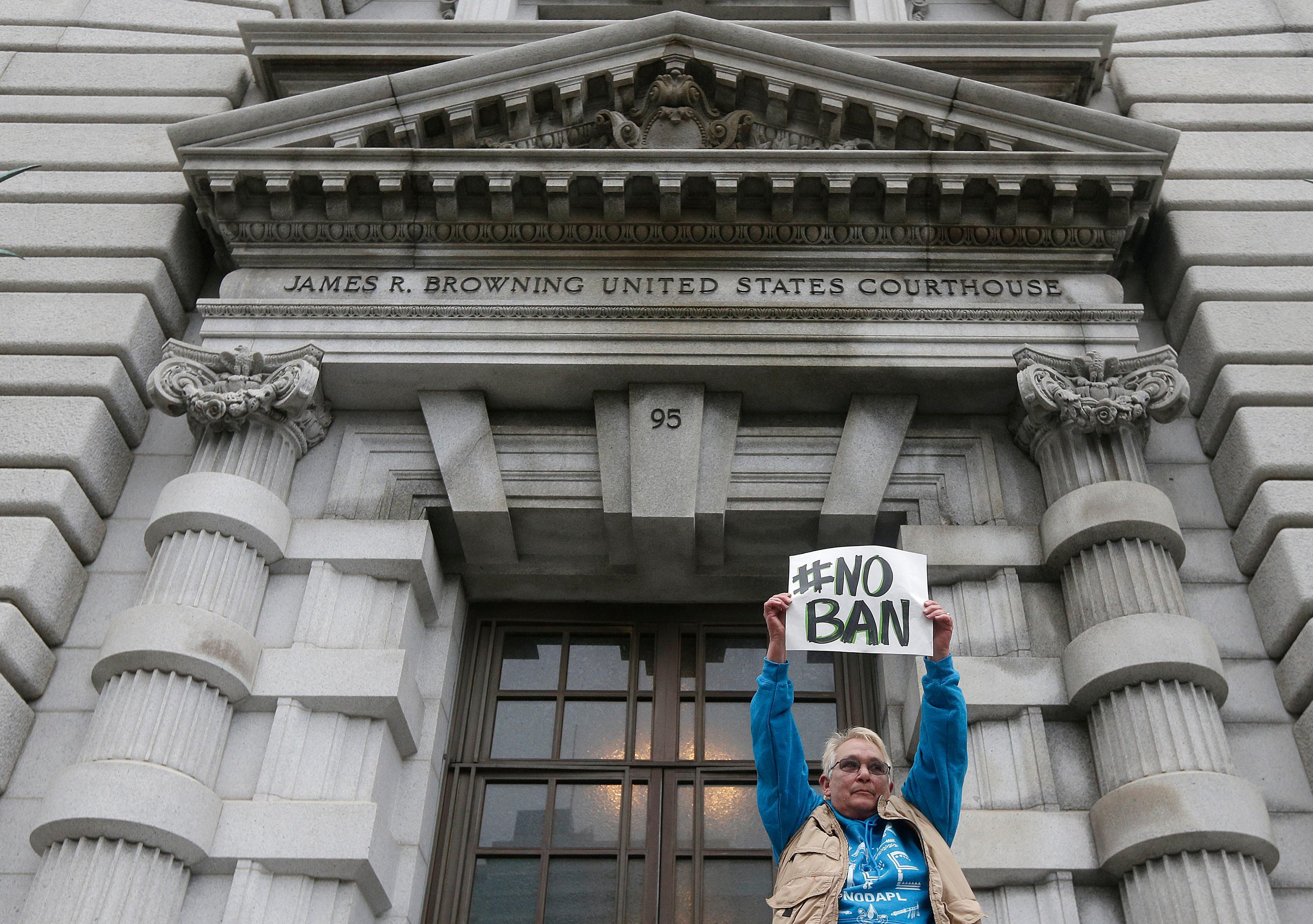 FILE- In this Feb. 7, 2017, file photo, Karen Shore holds up a sign outside of the 9th U.S. Circuit Court of Appeals in San Francisco.  (AP Photo/Jeff Chiu, File)