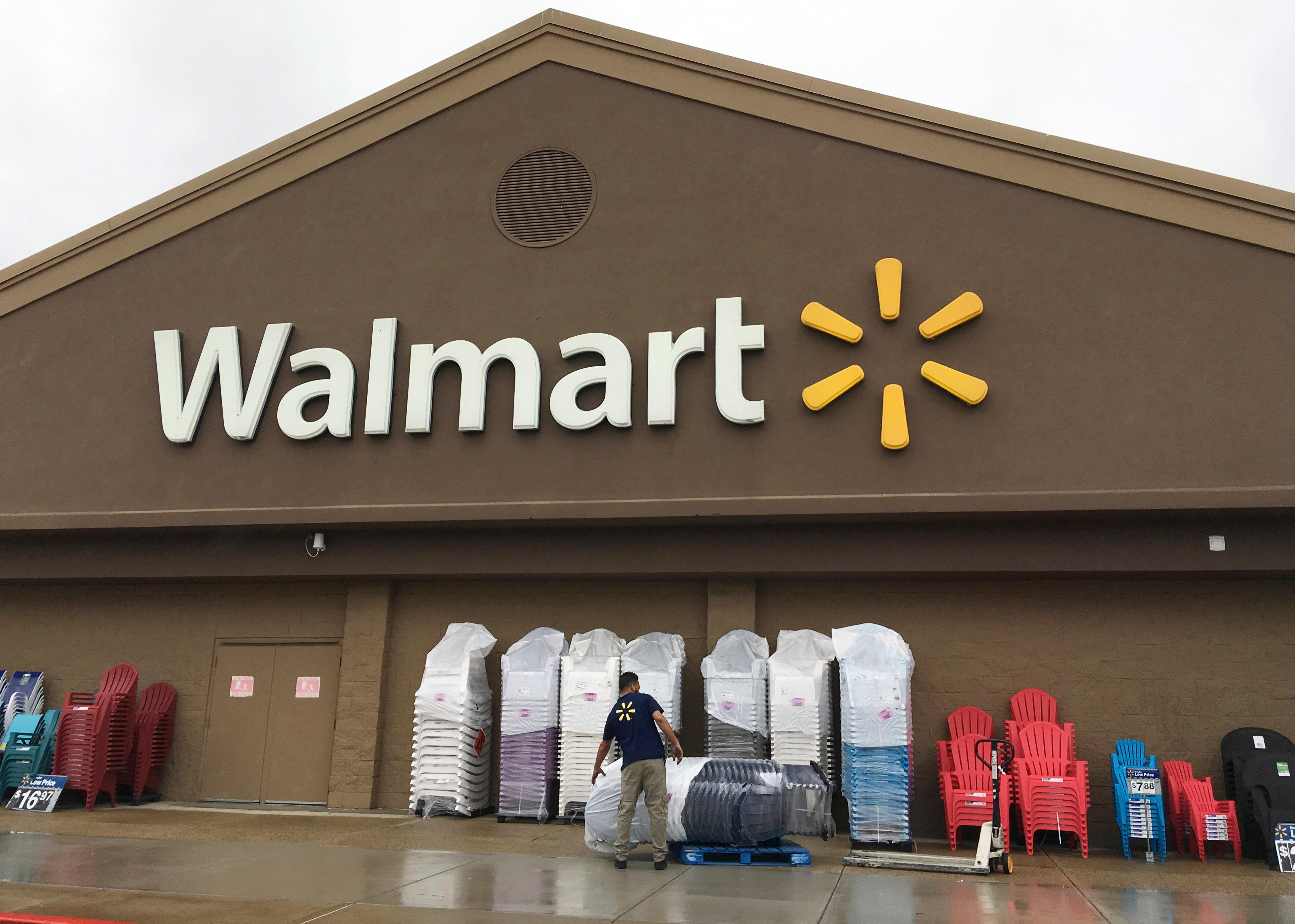 FILE - In this June 5, 2017, file photo, a worker stacks merchandise outside a Walmart in Salem, N.H. (AP Photo/Elise Amendola, File)