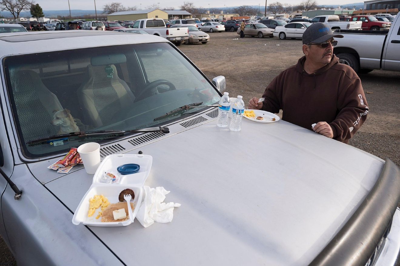 Todd Remocal of Biggs, Calif., eats breakfast on the hood of his truck at the Silver Dollar Fairgrounds on Monday, Feb. 13, 2017, in Chico, Calif. He and his wife Kelly slept in their vehicle with their three dogs last night after residents were evacuated from the area due to fears of a possible failure of the emergency spillway at the Oroville Dam.(Paul Kitagaki Jr./The Sacramento Bee via AP)